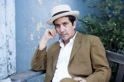 Dressed in a suit and hat, A.J. Croce sits on a bench outdoors.