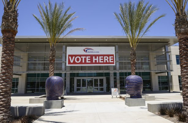 "A ""vote here"" sign hangs above the door at the San Diego County Registrar of Voters Office in Kearny Mesa on May 31, 2014."