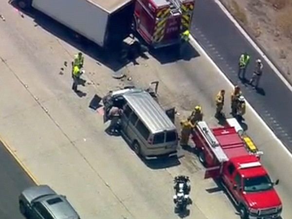 A silver van is shown next to the semi-trailer it collide...