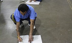 Inmates sit on the floor while drawing during an Arts-In-Corrections session.