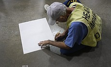 An inmate begins to draw on a piece of paper on the floor during an Arts-In-Corrections session.