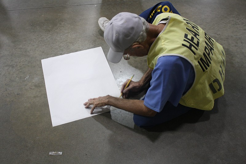An inmate begins to draw on a piece of paper on...