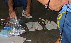 Inmates draw on paper with color pens during an Arts-In-Corrections program session.