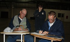 Inmates draw at desks during an Arts-In-Corrections session.
