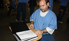 An inmate shares his pencil sketch during an Arts-In-Corrections session.