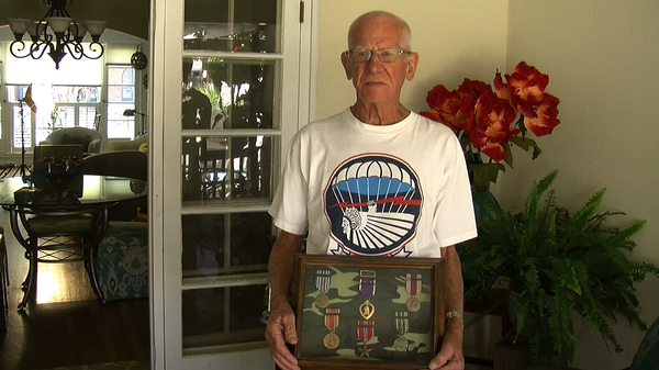 D-Day veteran Tom Rice holds up a case of awards he's received from fighting ...
