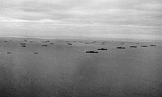 Ships carry Soldiers and equipment across the English Channel toward the coas...