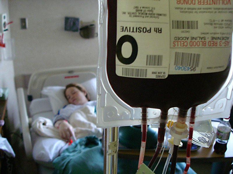 A woman receives a transfusion of donated blood while lying in a hospital bed...