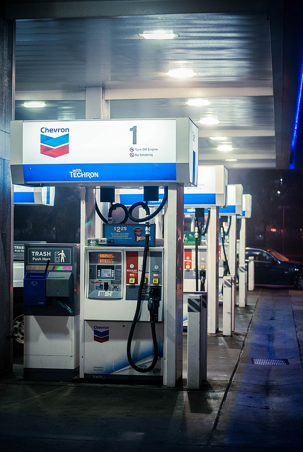 Light from gas pumps glow in the early morning darkness a...