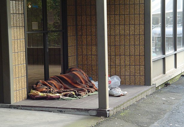 A homeless man sleeps outside a vacant commercial building, March 4, 2007.