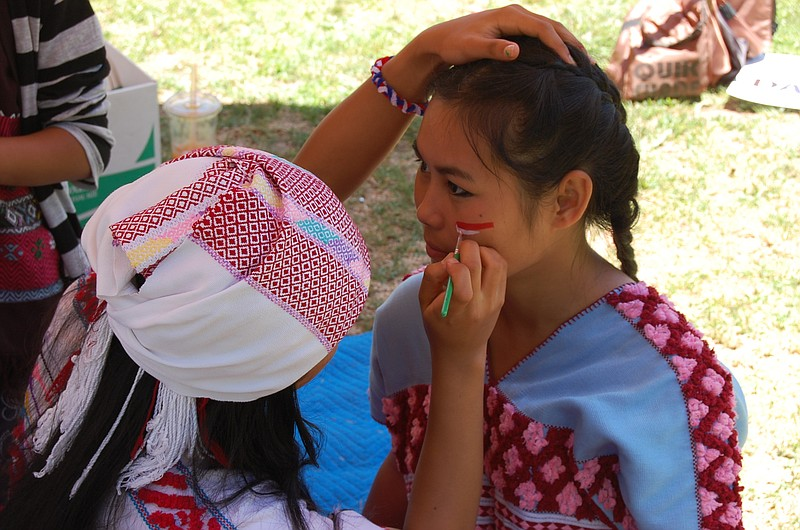 May Aye, a member of the Karen community in San Diego, has her face painted b...