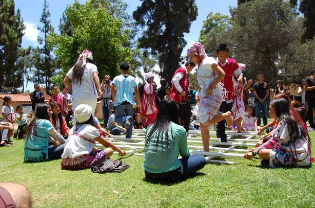 Karen youth perform a traditional bamboo dance during the World Refugee Day f...