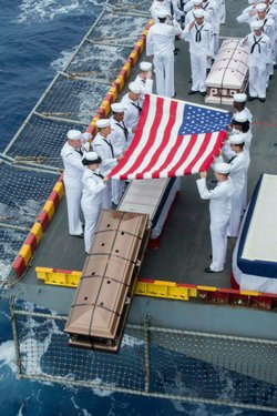 Sailors commit a casket into the sea during a burial at sea ceremony for 22 veterans and family members aboard the amphibious assault ship USS Peleliu (LHA 5).