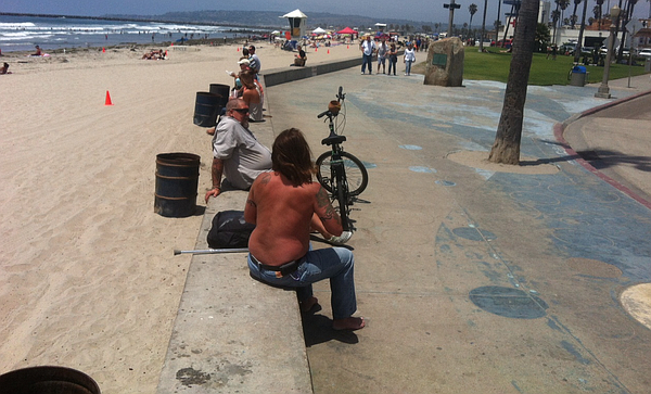 Beachgoers sit on the concrete wall that separates the sand from the sidewalk...