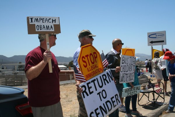 Protesters hold signs along a road in Murrieta, July 1, 2...