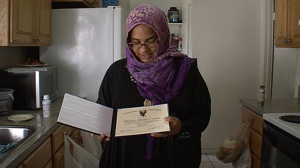 Khadija Osman shows off her diploma from Arroyo Paseo Charter High School Jul...