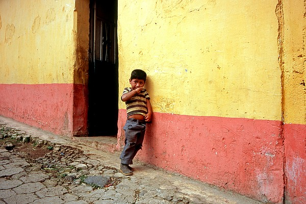 A child in Guatemala leans against a colorfully painted wall, Jan. 3, 2010.