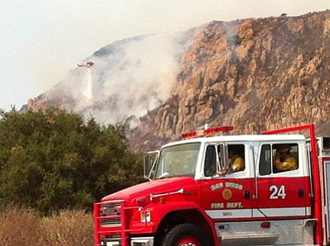 A helicopter makes water drops on a brush fire that broke...