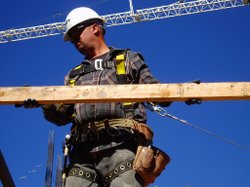 A construction worker wearing fall protection guides a piece of wood into pla...
