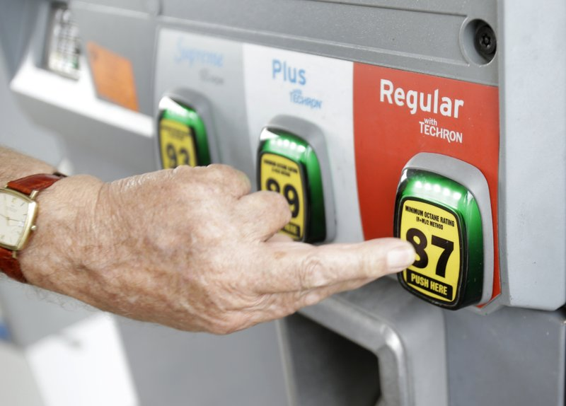 A man selects a grade of gasoline as he fills up his car at a gas station, Ju...