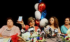 Attorney Gloria Allred holds up a card with sex...