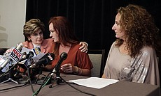 Attorney Gloria Allred, left, puts an arm aroun...