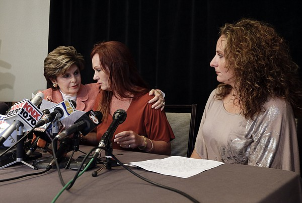 Attorney Gloria Allred, left, puts an arm around nurse Mi...