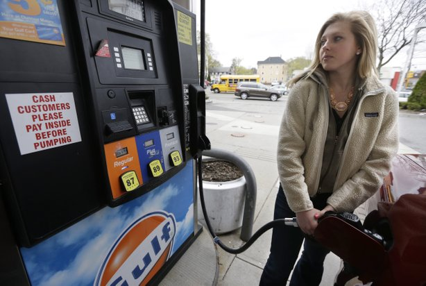 Katie Spillane, of Brookline, Mass., fills her car with fuel at a gas station...