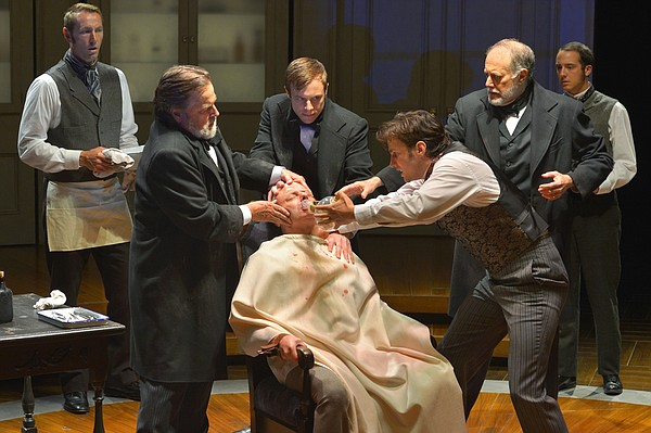 The actor playing William Morton administers ether via a glass tube to a pati...