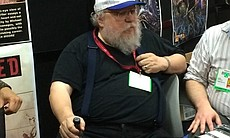 """Game of Thrones' author George R. R. Martin sits at a Comic-Con booth, July 23, 2014."