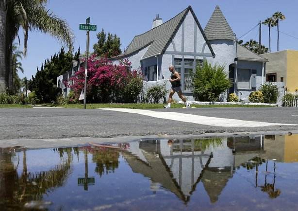 A house on Texas Street is reflected in a puddle of water from an irrigated f...