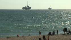 Two offshore oil rigs loom off the coast of Huntington Beach, July 20, 2014.