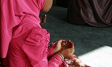 City Heights resident Gediya, 7, performs Dua, a call to God for help, mercy and forgiveness during one of the five daily prayers of Ramadan, July 28, 2014. Her cupped hands represent a plea of hope, praise and thanks.  The five prayers are called Salat al-Fajr, Zuhr, Asr, Maghhrib and Isha. The early morning prayer, Salat al-Fajr, marks the beginning of fasting for the day and Maghhrib breaks the day's fast.