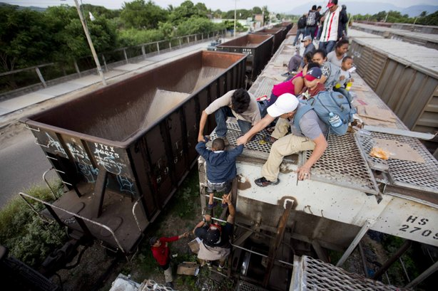 A young boy is helped down from the top of a freight car, as Central American...