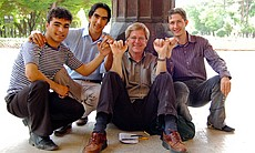 Rick Steves sits with three young men in Iran. Hooking fingers seems to be human nature — we can be friends and can get along.