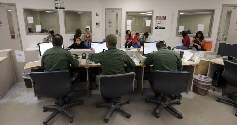 U.S. Customs and Border Protection agents work at a processing facility in Br...