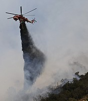 A helicopter drops retardants while battling the Cocos fire in the San Marcos area, May 15, 2014.