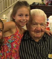 "USS Indianapolis survivor Verlin ""Buzz"" Fortin poses with his great-granddaughters at the Golden Oaks Senior Living Community in Yucaipa, California, on July 30, 2014."