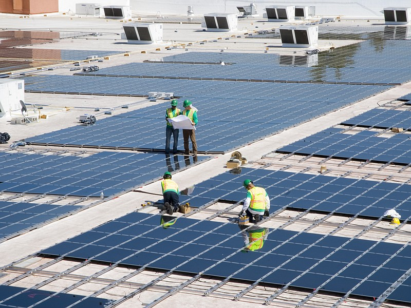Workers install thin film solar panels onto the roof of a Walmart in Mountain...