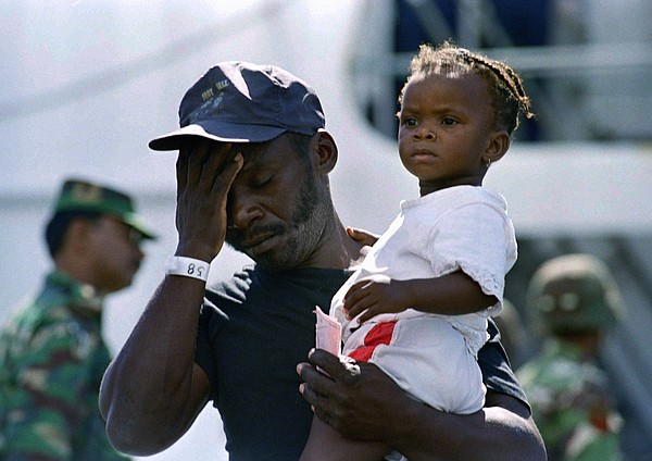 A Haitian man carrying his daughter leaves the U.S. Coast Guard ship Valiant ...