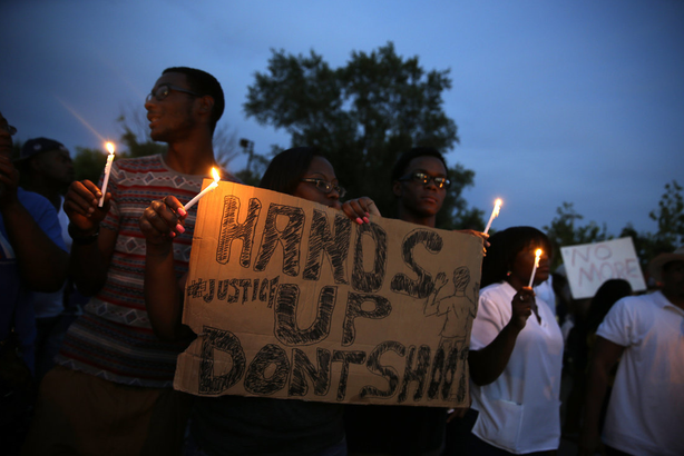 Demonstrators hold candles and signs Thursday in Ferguson, Mo. Hundreds of people protesting the death of Michael Brown marched through the streets of Ferguson alongside state troopers on Thursday.