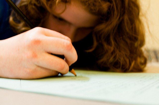 A young girl leans in close to her workbook and tries to focus on her writing...