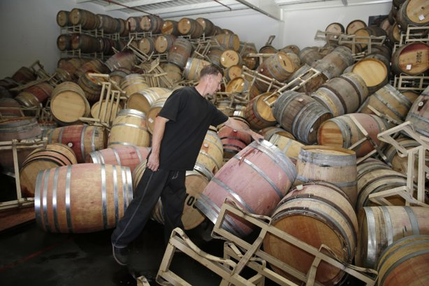 Cellar worker Daniel Nelson looks over toppled barrels of Cabernet Sauvignon following an earthquake at the B.R. Cohn Winery barrel storage facility in Napa, Aug. 24, 2014.