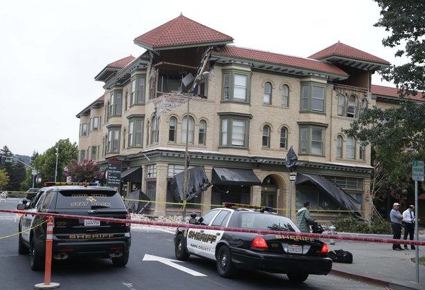 Police cars block the street outside a heavily damaged building in Napa following an early morning earthquake Sunday, Aug. 24, 2014.