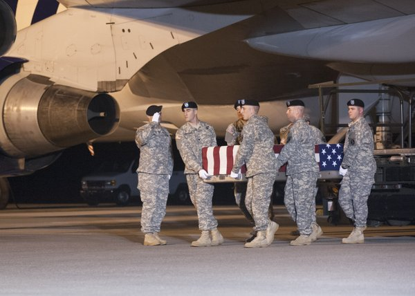 A U.S. Army carry team transfers the remains of Sgt. Chri...
