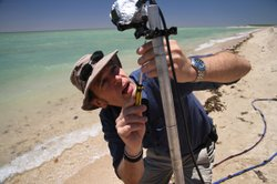 Mark Evans sets up a shark deterrent test on the beach.