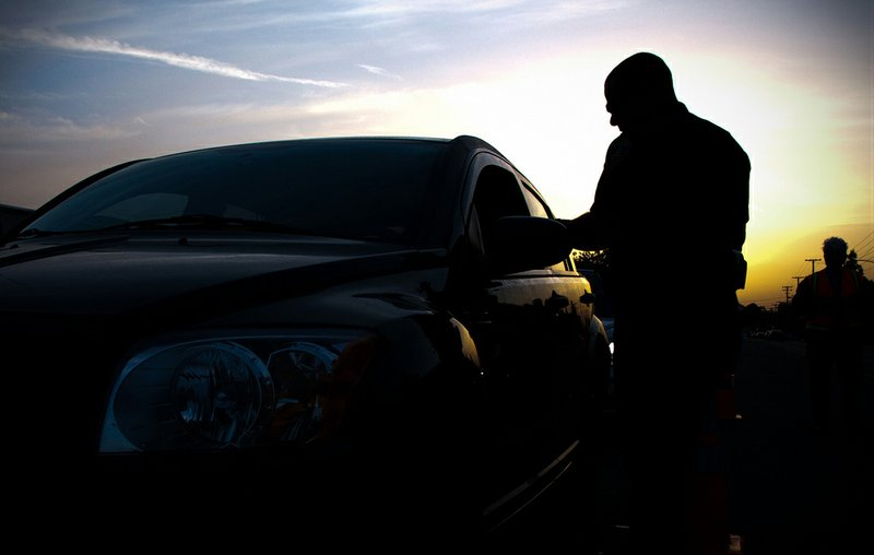 A law enforcement officer stops a vehicle at a DUI checkpoint in Riverside, C...