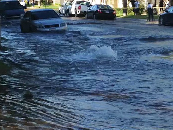 A car is surrounded by water after a water main ruptured ...