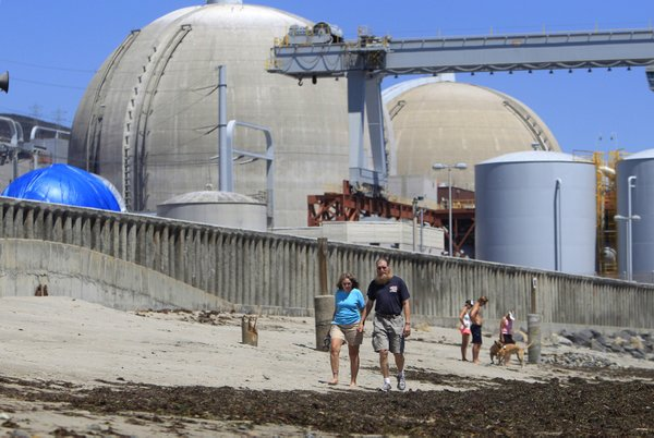 Beachgoers walk on the sand near the San Onofre nuclear p...