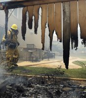 A firefighter puts water on a house fence in Carlsbad, California, May 14, 2014.
